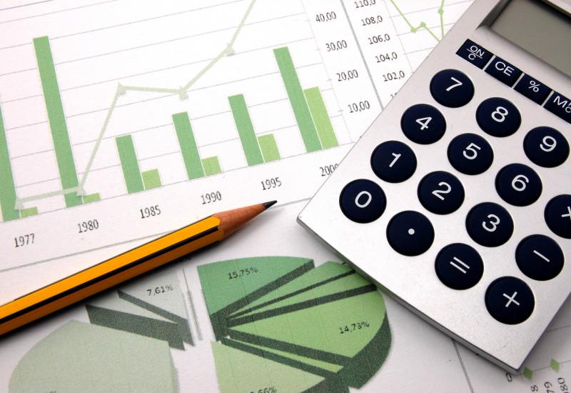 auf einem Tisch liegen ein Blatt Papier mit in grün und weiß gehaltenen Diagrammen, ein Taschenrechner und ein Bleistift