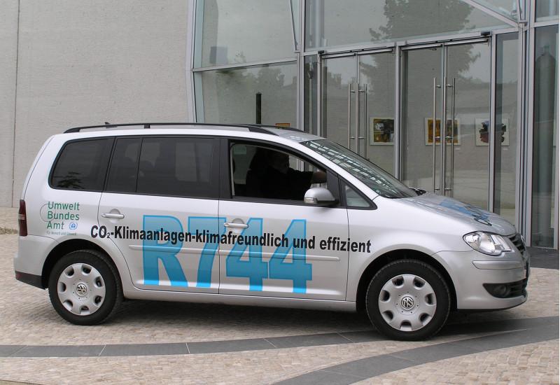 """ein silbergrauer VW Touran steht vor dem UBA Dessau-Roßlau. Er trägt die Beschriftung """"CO2-Klimaanlagen - klimafreundlich und effizient, R744"""" und das Logo des Umweltbundesamtes"""