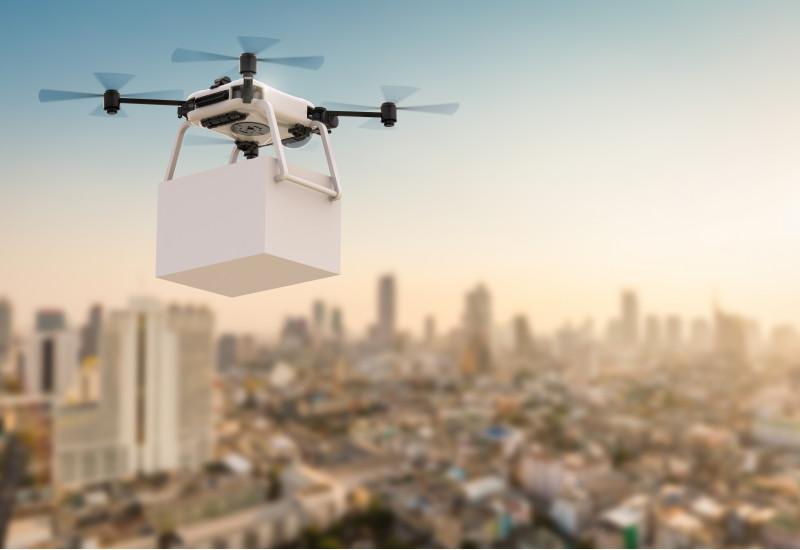 eine Drohne fliegt mit einem Päckchen über eine Stadt