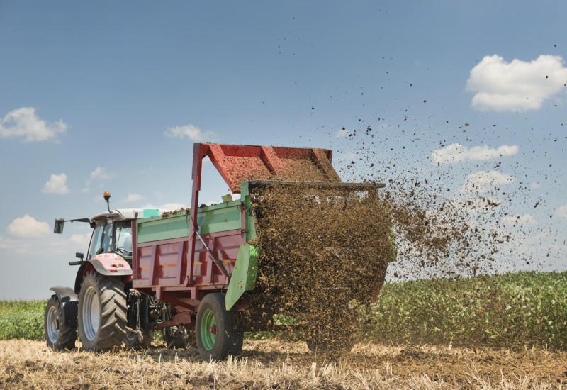 ein Traktor bringt Mist auf einem Acker aus