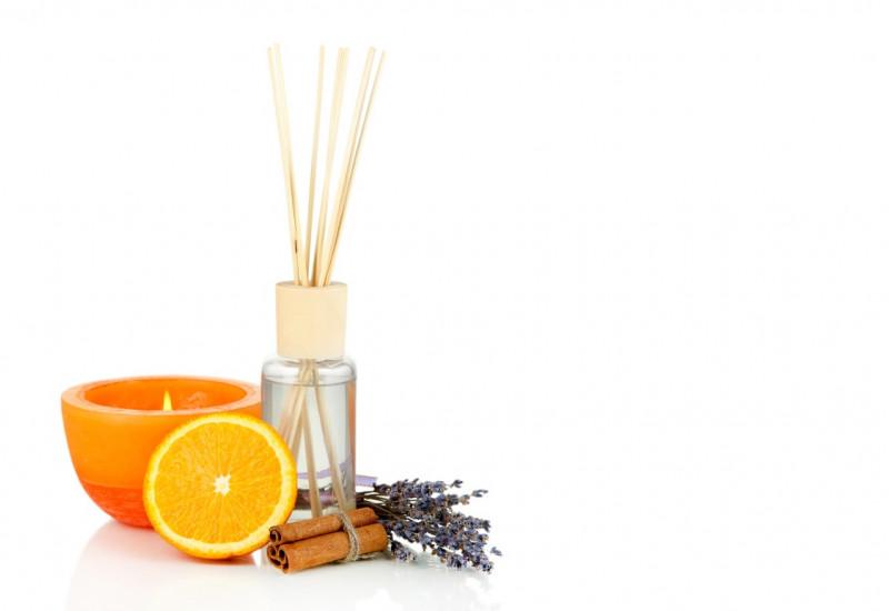 eine orange Duftkerze, ein Aromafläschchen mit Holzstäbchen zur Raumluft-Beduftung, eine halbe Orange, ein Lavendelsträußchen und Zimtstangen