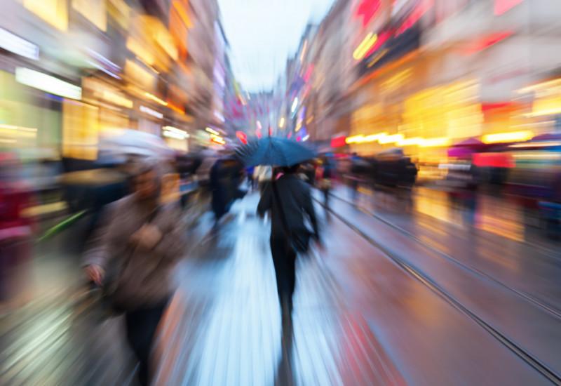 Menschen in einer Einkaufsstraße bei Regen und Dämmerung