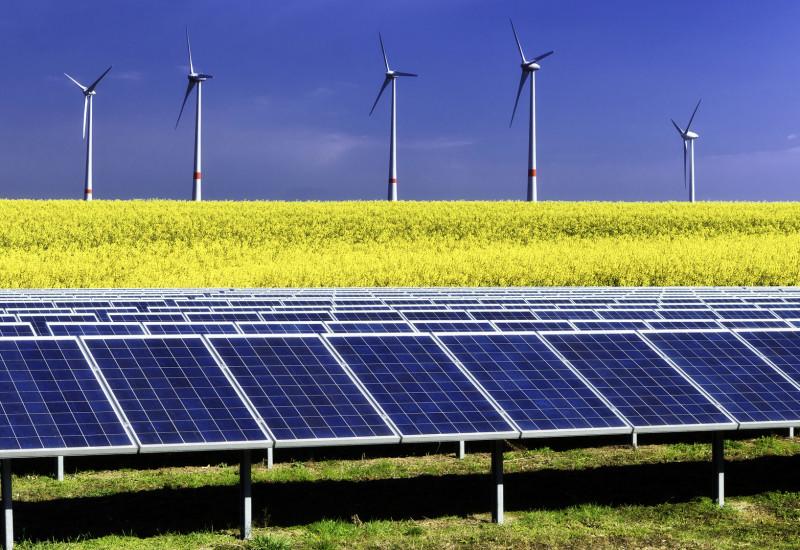 Foto einer Fotovoltaik-Anlage auf einer Wiese, dahinter ein Rapsfeld und dahinter Windkraftanlagen vor blauem Himmel