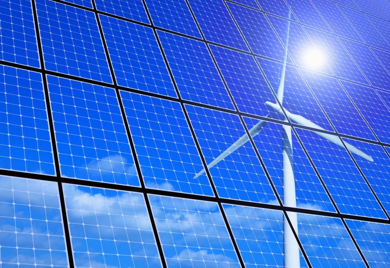 eine Windkraftanlage, die Sonne und Schönwetterwolken an einem blauen Himmel spiegeln sich in Solarzellen