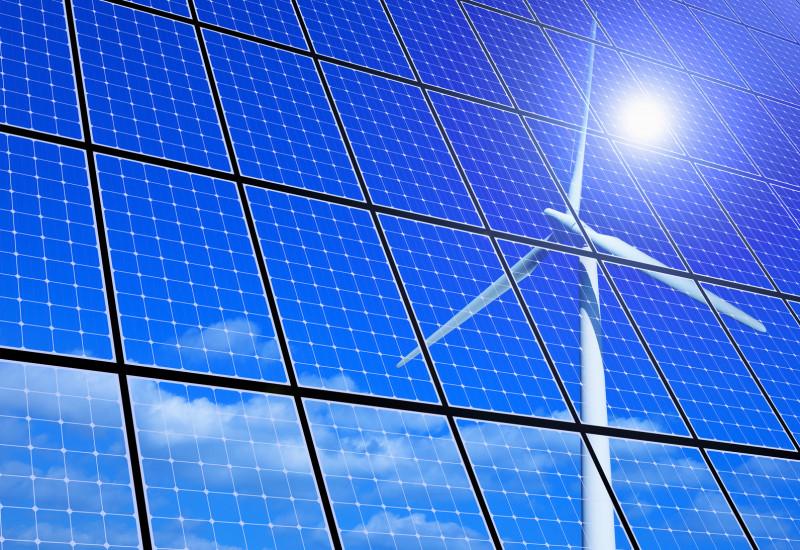 Die Sonne und ein Windrad spiegeln sich in einer Fläche von Solarzellen