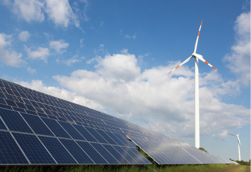 Windkraftanlagen und Solarpanels auf einer Wiese