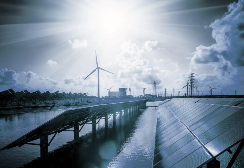 in einer futuristisch anmutenden Szenerie mit blauem Licht stehen Solarpanels auf einer Wasserfläche, im Hintergrund Windkraftanlagen und Strommasten