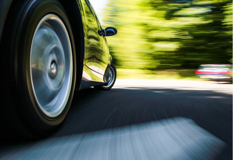 ein Auto fährt über eine Fahrbahn, man sieht den rechten Hinterreifen in Großaufnahme