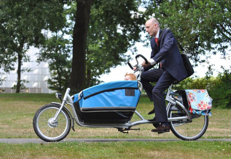 Mann im Anzug auf einem Fahrrad, hinten mit Fahrradtaschen auf dem Gepäckträger, vorne ein Kind in einem ins Fahrrad integrierten Wagen
