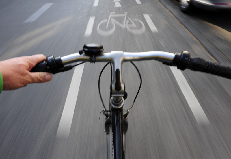 Foto eines Fahrradlenkers von einem Fahrradfahrer, der auf einem Radweg fährt
