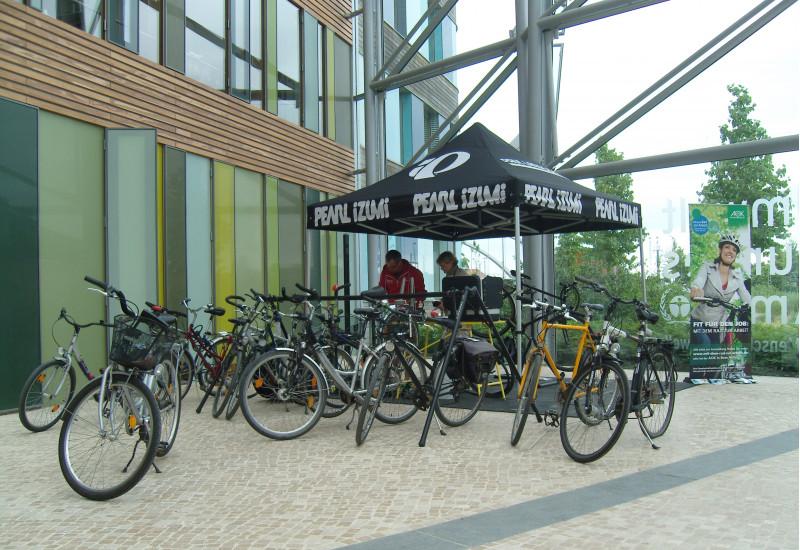 """im Eingangsbereich des UBA-Dienstgebäudes Dessau werden Fahrräder repariert, im Hintergrund ein Werbeplakat für die Aktion """"Mit dem Rad zur Arbeit"""""""