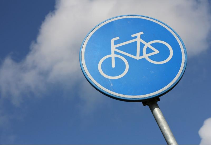 blaues Verkehrsschild für Fahrradweg vor blauem Himmel mit weißen Wolken
