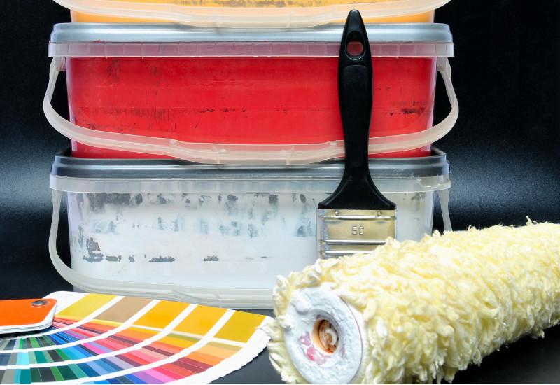 verschiedenfarbige Wandfarben in niedrigen Eimern, davor ein Fächer mit Farbmuster-Bögen, ein Pinsel und eine Rolle zum Wändestreichen
