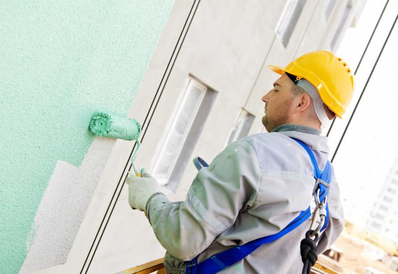 ein Mann im Blaumann und mit gelbem Schutzhelm ist dabei, mit einer Rolle eine Hausfassade mintgrün anzustreichen