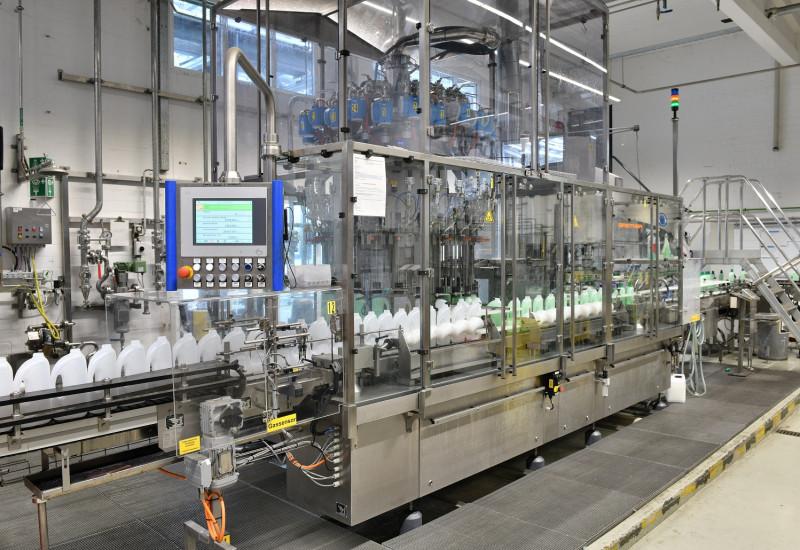 In einer Fabrikhalle stehen leere Kunststoffflaschen auf einem Fließband und werden befüllt.