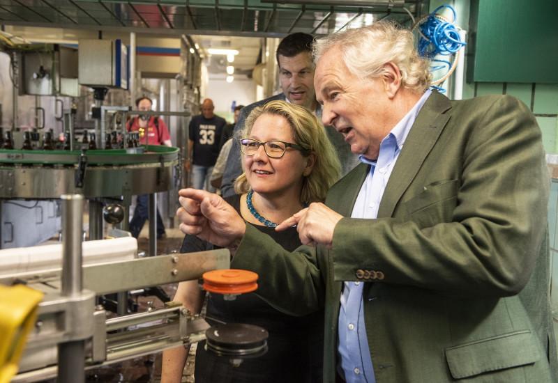 Bundesumweltministerin Schulze lässt sich die Flaschenwaschmaschine erklären
