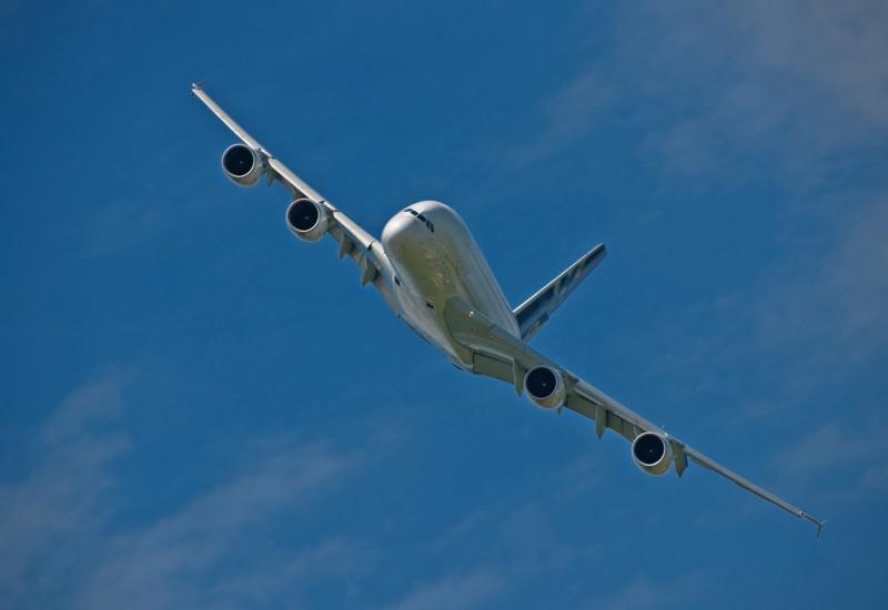 fliegendes Flugzeug mit vier Triebwerken vor blauem Himmel