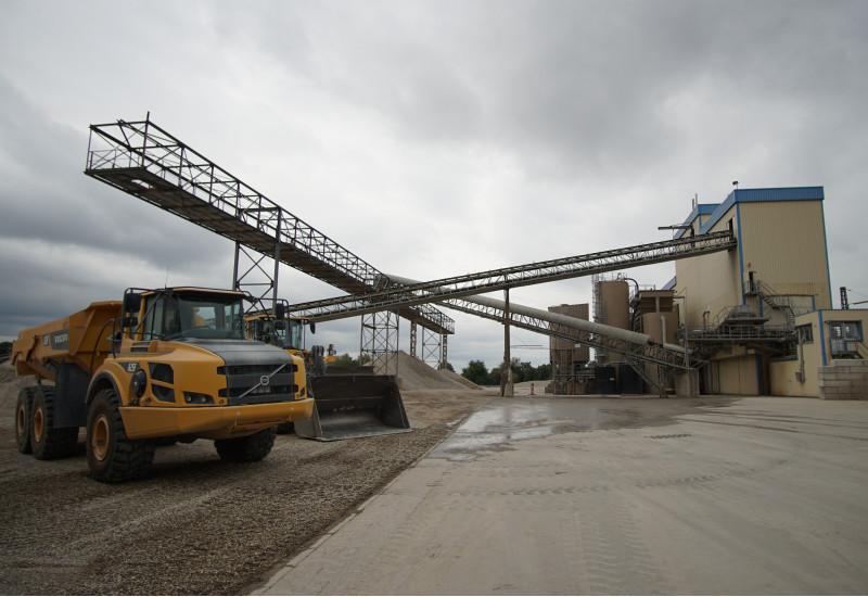 Foto einer Industrieanlage, davor zerkleinertes Gestein und ein Muldenkipper