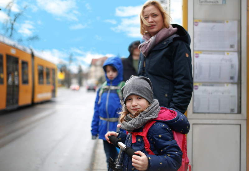 Familie an der Straßenbahnhaltestelle