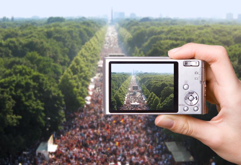 """Digitalkamera fotografiert eine Großveranstaltung auf der Berliner """"Straße des 17. Juni"""", rechts und links der baumbestandene """"Große Tiergarten"""""""