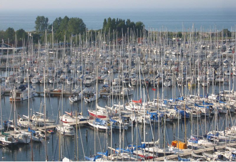 A sea harbor with many small sail and motor boats.