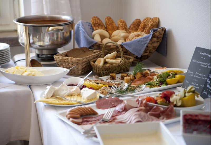 Frühstücksbuffet im Hotel mit Brötchenkorb und Porzellanplatten mit unverpackten Lebensmitteln wie Butter, Käse und Wurst-Aufschnitt