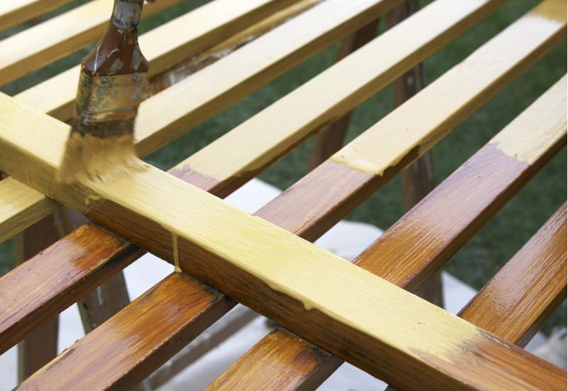 ein Holzzaun wird mit einem Pinsel gestrichen