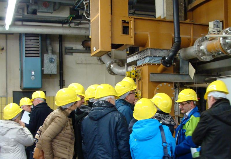 eine Gruppe Menschen mit gelben Schutzhelmen schaut sich eine technische Anlage an