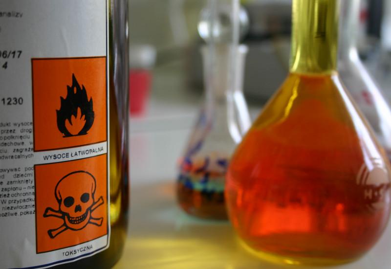 """auf einem Tisch stehen Flacons mit Flüssigkeiten und eine Flasche mit Warnsymbolen """"Flamme"""" und """"Totenkopf"""""""