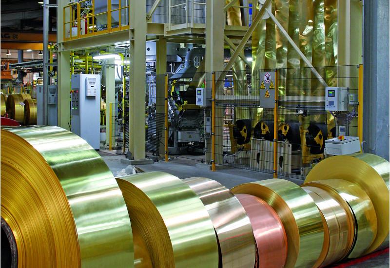 in einer Fabrikhalle liegen mehrere Rollen mit aufgerollten Messingbändern