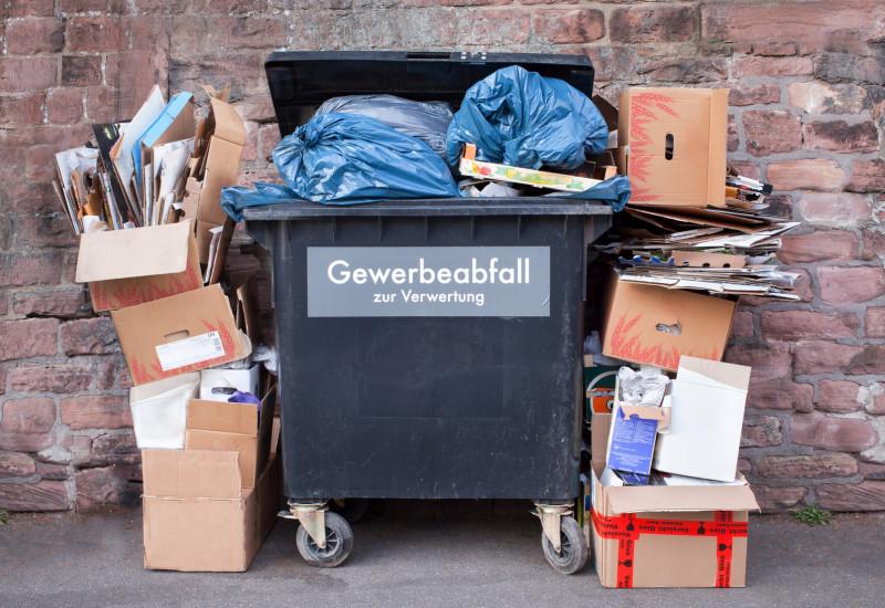"""überquellender Müllcontainer in einem Hinterhof mit der Aufschrift """"Gewerbeabfall zur Verwertung"""", daneben türmen sich leere Kartons"""