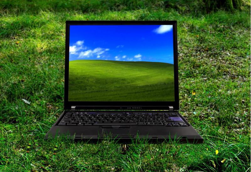 ein Laptop steht auf einer grünen Wiese, auf dem Bildschirm ist ein grüner, grasbewachsener Hügel vor blauem Himmel zu sehen