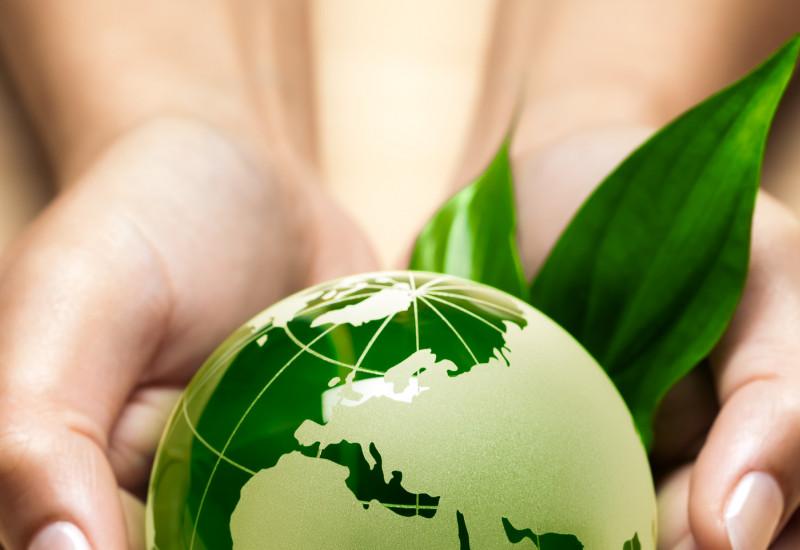 eine Frau hält vorsichtig eine grün leuchtende Erdkugel in den Händen