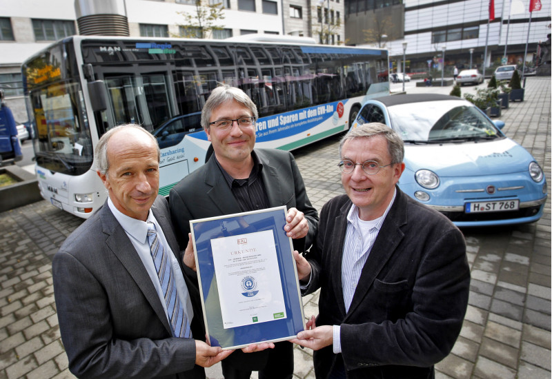 """three man holding a document with the """"Blue Angel"""" edolabel, in the background a bus"""