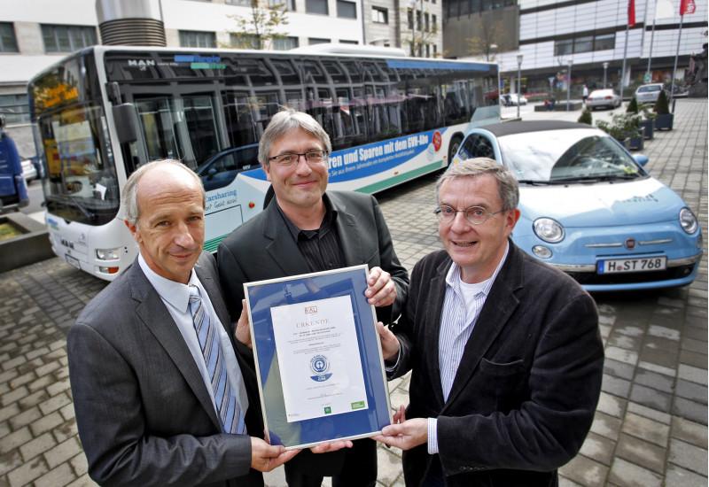 """drei Männer halten eine Urkunde mit dem Umweltzeichen """"Blauer Engel"""", im Hintergrund steht ein Linienbus"""