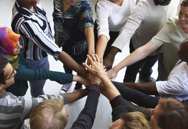 Frauen und Männer mit verschiedenen Hautfarben, mit und ohne Kopftuch stehen in einem Kreis und halten ihre Hände gemeinsam in die Mitte aufeinander