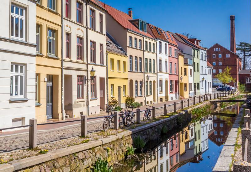 Häuserzeile mit verschiedenfarbigen Fassaden an einem Kanal in der Stadt