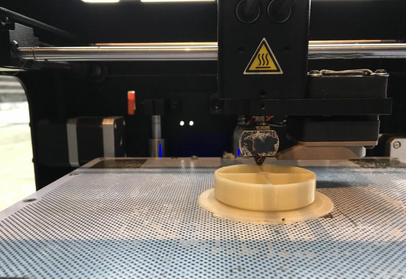 auf einer gelochten Metallplatte ist ein Plastikgegenstand zu sehen, über den der Druckkopf eines 3D-Druckers fährt
