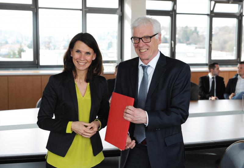 eine Frau und ein Mann posieren mit einem roten Hefter für ein Foto, im Hintergrund weitere Männer in Anzügen im Gespräch in einem Besprechungsraum