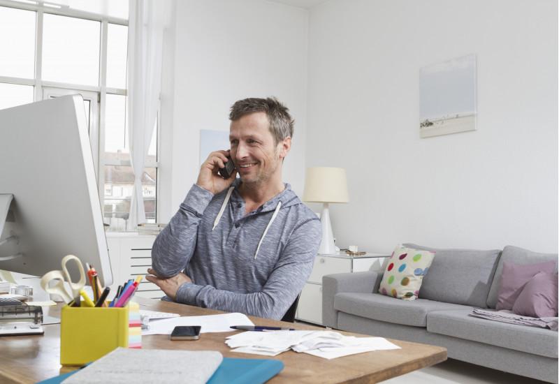 ein Mann sitzt in einem Wohnzimmer am Computer und telefoniert