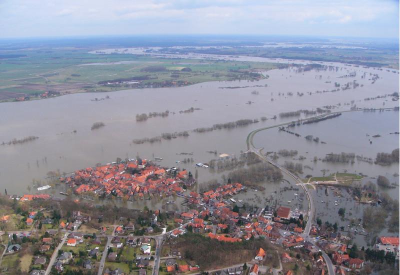 Luftbild: eine Landschaft mit einer Siedlung ist großflächig überschwemmt