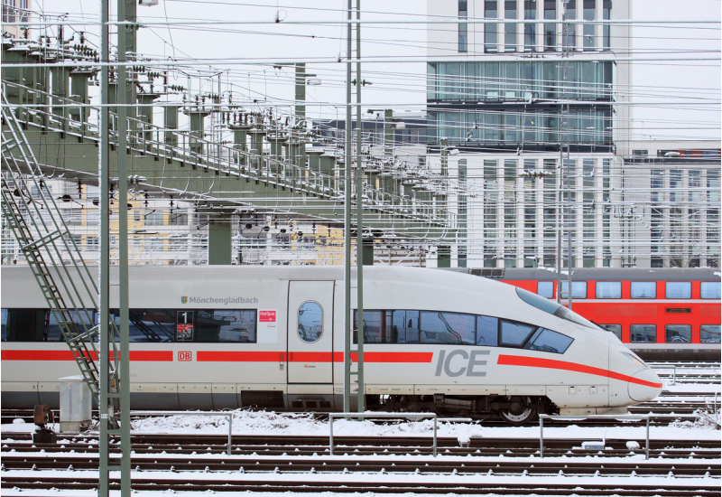 moderner ICE-Schnellzug auf einem verschneiten Gleis in der Stadt