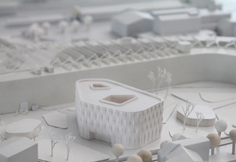 von Architekten gebautes, ganz in weiß gehaltenes Modell eines modernen vierstöckigen, polygonalen Flachbaus und seiner Umgebung