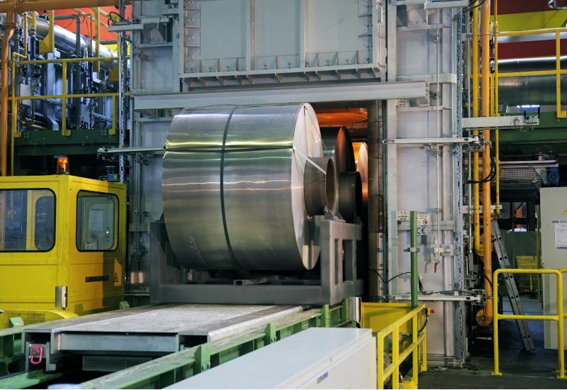 in einer Fabrikhalle wird ein große Rolle aufgerolltes Aluminiumband auf einem Förderband in eine Kammer gefahren, in der es glüht