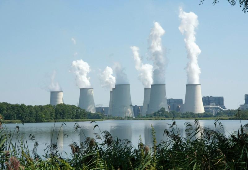 dampfende Kühltürme eines Kraftwerks an einem Gewässer