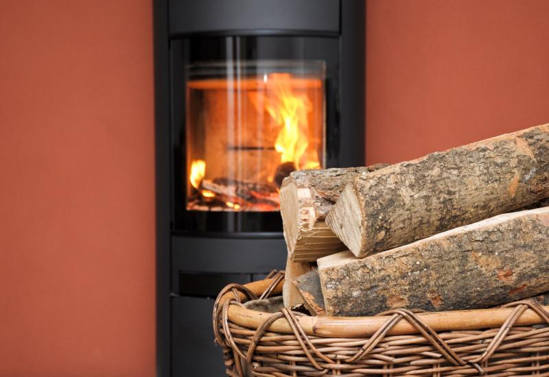 Vor einem brennenden Kaminofen steht ein Korb mit Scheitholz