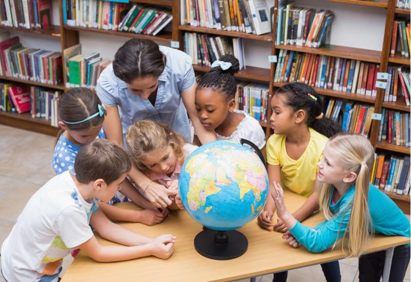 Kinder mit und ohne Migrationshintergrund schauen sich mit einer Betreuerin in einer Bibliothek einen Globus an.