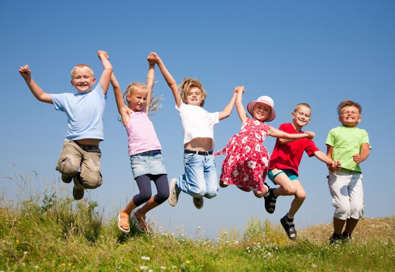 Sechs Kinder auf einer blühenden Wiese vor blauem Himmel haben sich in einer Kette bei den Händen gefasst und hüpfen lachend in die Luft