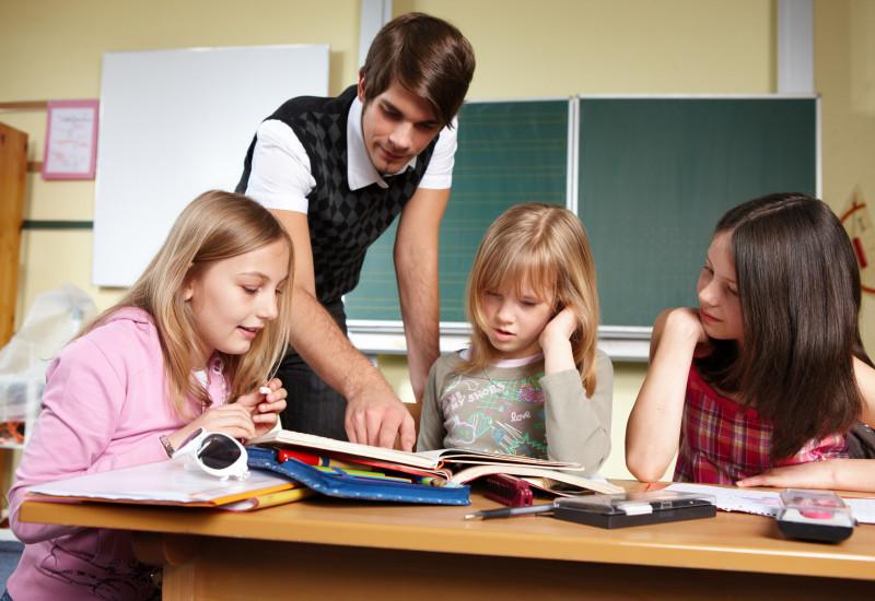 ein junger Leerer und drei Schulkinder sind an einem Tisch in einem Klassenzimmer über Hefte gebeugt