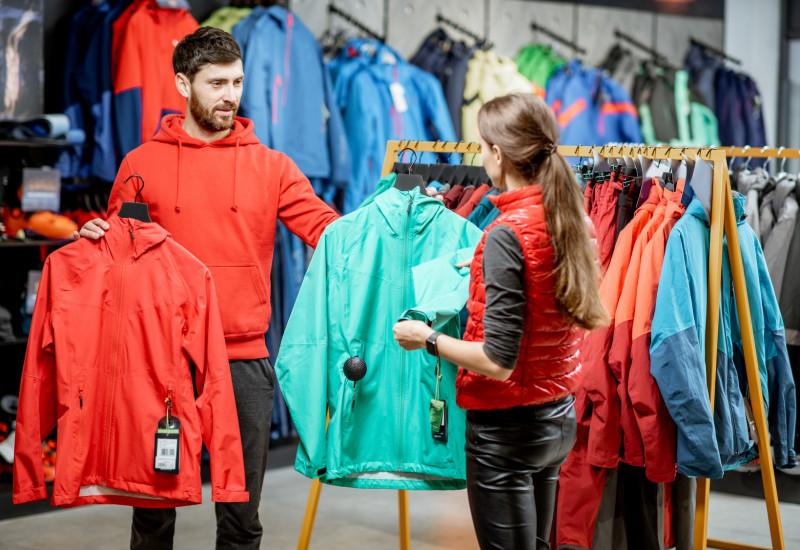 ein junges Pärchen sucht in einem Geschäft zusammen eine wetterfeste Jacke aus